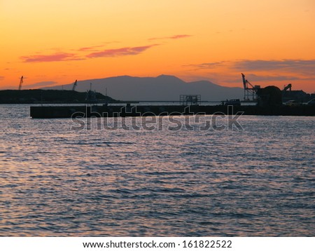 A mountain on the horizon with a dock in the foreground. - stock photo