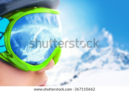 A mountain range reflected in the ski mask.Shallow depth of field. - stock photo