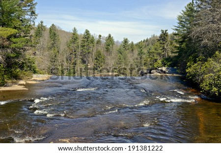 A mountain river flowing over the rocks down to a waterfall. - stock photo