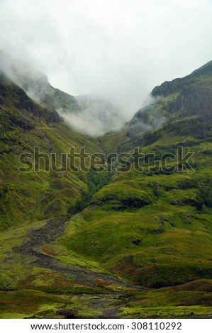 A mountain river running down misty mountains in the Scottish Highlands - stock photo