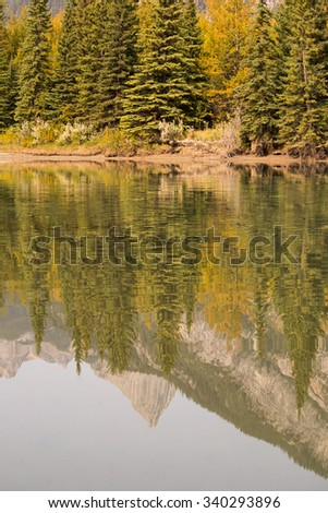 A mountain scene reflected in the clear, calm waters of the Bow river.