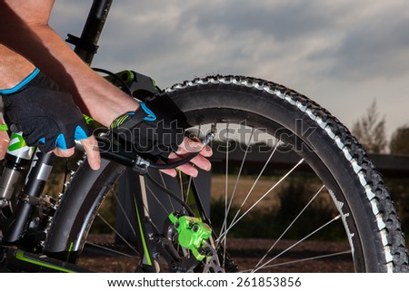 A Mountainbiker is filling his bike with air. - stock photo