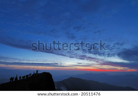 A mountaineer and the top of the break of day - stock photo