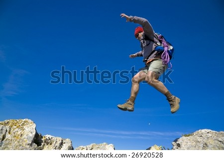 A mountaineer jumping trough the rocks, over a clear blue sky - stock photo