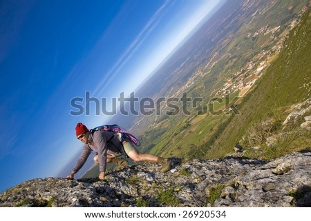 A mountaineer man, climbing a steep cliff - stock photo