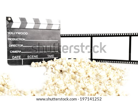 A movie clapboard sitting near a pile of popcorn.