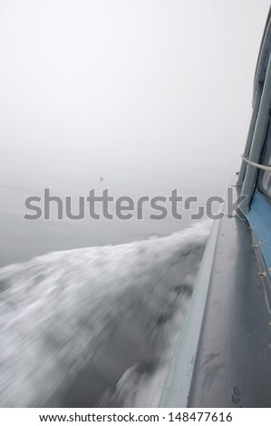 A moving boat with blurred water and wake