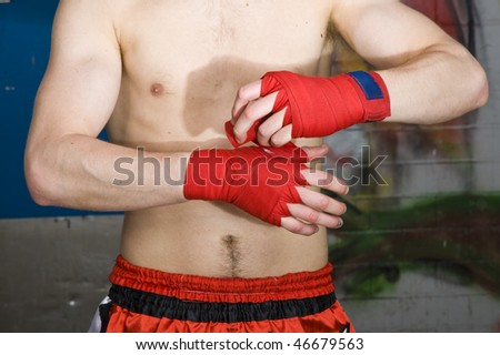 A muay thai fighter bandaging his hands before a fight - stock photo
