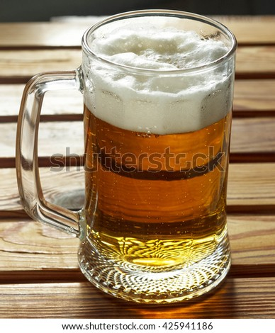 A mug of beer with froth closeup. Glass of beer on a wooden table  - stock photo