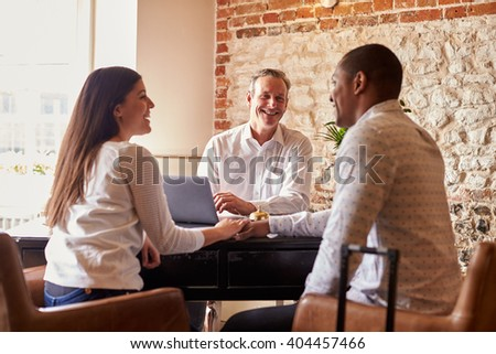 A multi ethnic couple checking in at a boutique hotel - stock photo