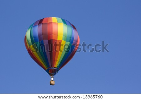 A multicolored hot air balloon floats in the blue sky