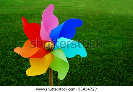 A multicolored pinwheel stands with a beautiful green grassy field - stock photo