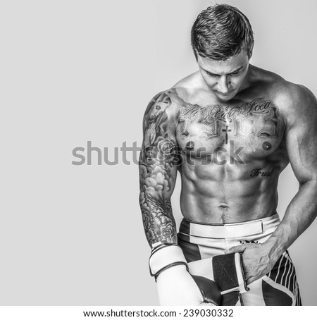 A muscled tattooed man putting on boxing gloves