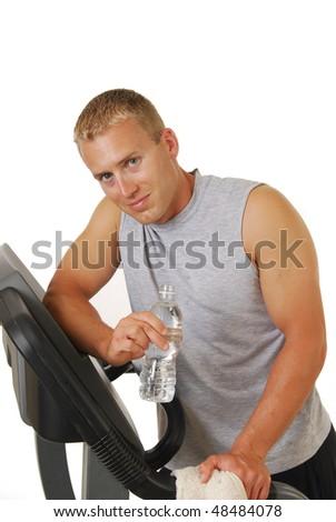 A muscular blond man on a treadmill - stock photo