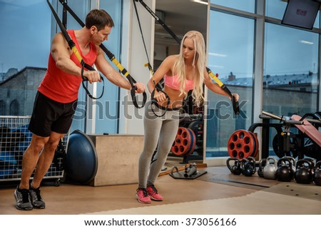 A muscular man and an athletic woman doing exercises with expander in a gym.
