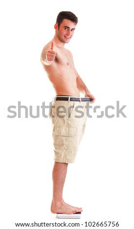 A muscular man showing how much weight he lost thumb up - stock photo