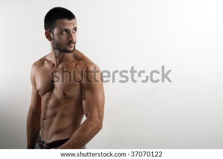 a muscular man with naked torso staring back on a white background