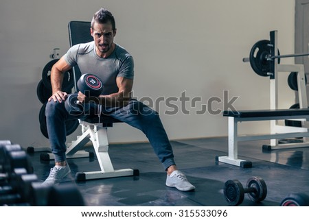 A muscular young man working out in the gym. Dramatic light, deep shadows, enhanced highlights, toned image, selective focus. - stock photo