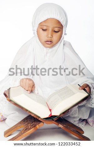 A muslim girl wearing praying attire reading the holy quran - stock photo