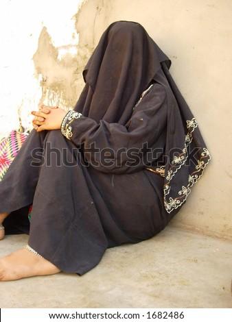 a muslim lady sitting in a village in india - stock photo