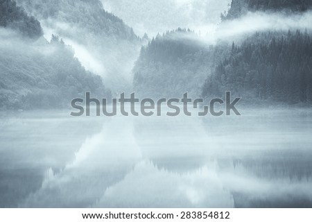 A mystical fjord in Norway with mountains and fog hanging over the water in a beautiful monochrome blue color. - stock photo