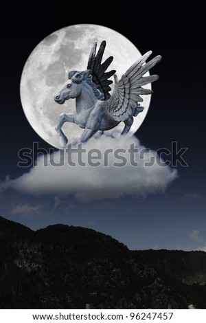 A mythical pegasus flying across a full moon over a remote hillside. - stock photo
