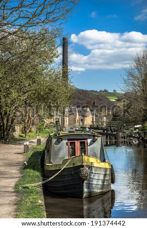 A narrow boat mored along the historic Rochdale canal near Todmorden  with old mill chimney in the background.
