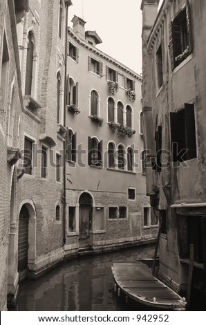 A narrow canal lined with homes in Venice - sepia toned. - stock photo