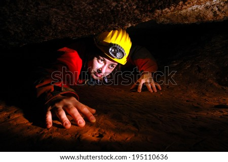 A narrow cave passage with a cave explorer  - stock photo