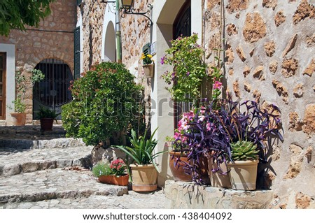 A narrow street with flowers in the center of Fornalutx which is a mountainous municipality and village on Mallorca and one of the most attractive villages on the west coast