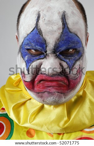 A nasty evil clown, angry and looking mean.
