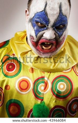 A nasty evil clown, angry and looking mean. Harsh lighting, focus on the teeth.