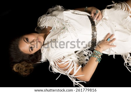 A Native American woman laying in her Native dress looking up. - stock photo