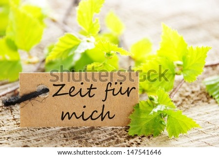 a natural looking label with green leaves and the german words Zeit fuer mich which means time for myself and wood as background - stock photo
