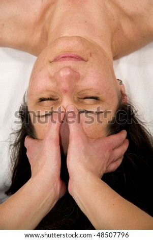a natural mature woman having a massage at the root of her nose