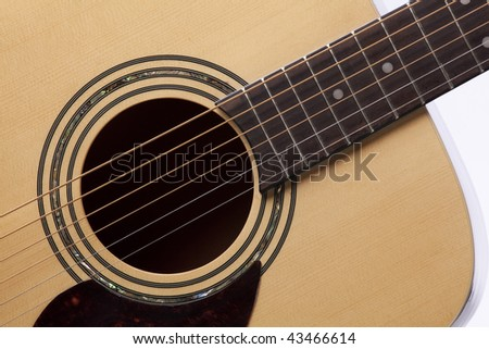 a natural wood  finish acoustic guitar isolated close  up on a white background.
