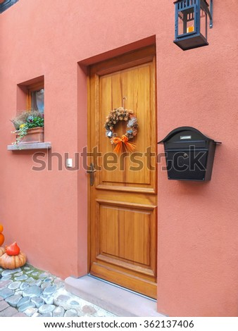 A nature wooden front door to a home . There is a color wall with nice wall lamp and postbox. Vertical shot. - stock photo