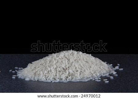 A neat pile of rice sitting on the worksurface in my kitchen, isolated on black