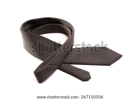 a neatly folded black tie with small white dots lies in a curve on a white isolated background. - stock photo