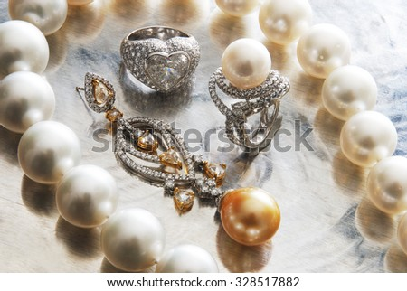 a necklace with pearls with an earring and rings in a close up - stock photo