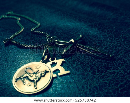 A necklace with three pendants: a letter k, a cross and the taurus zodiac sign