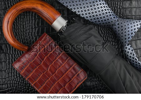A necktie, wallet, umbrella  lying on the skin, can be used as background - stock photo