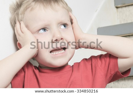 A Neglected lonely child leaning at the wall ear close with his hand - stock photo