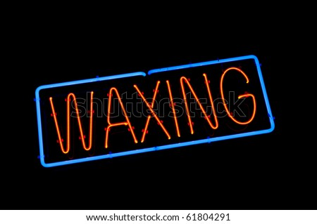 A neon sign in a shop window indicates waxing is offered by this business.