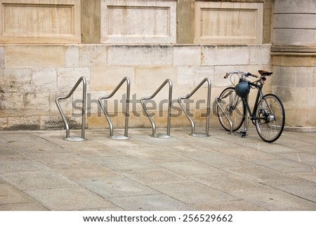 A new bike parked in an empty metal rack  close to a old stone building in Luxembourg. - stock photo