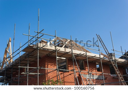 A new-build house, with scaffolding erected for the builder to complete the roof. - stock photo