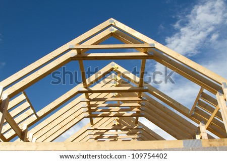 A new build roof with a wooden truss framework making an apex against a blue sky with cloud. - stock photo