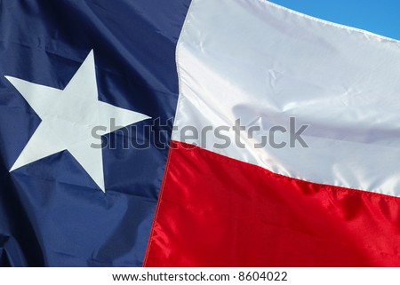 A new flag is replacing an old worn flag. - stock photo