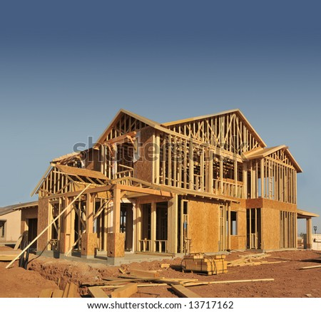 A new home being built with wood, trusses and supports - stock photo