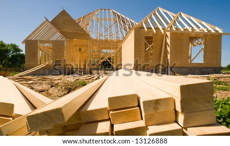 A new home being built with wood, trusses, supports and a foundation.
